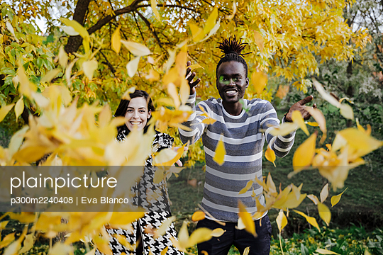 Happy multi ethnic couple throwing leaves while standing in park during autumn - p300m2240408 by Eva Blanco