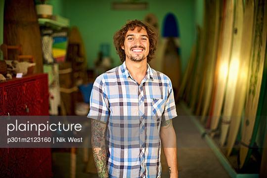 Portrait confident, happy male surf shop owner - p301m2123160 by Nik West