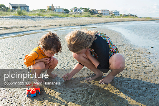 Caucasian brother and sister searching on beach - p555m1522768 by Marc Romanelli
