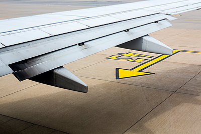 The edge of a jet aircraft wing as it is parked on the apron with painted arrow on the ground. - p1057m2020728 by Stephen Shepherd