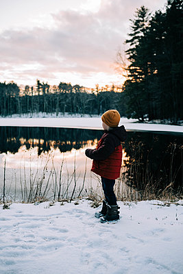 Little boy by a half frozen lake during sunset. - p1166m2157332 by Cavan Images