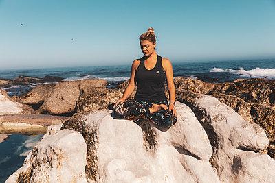 Junge Frau meditiert auf einem Felsen am Meer - p1640m2261154 von Holly & John