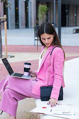 Young female entrepreneur with laptop checking papers while sitting on retaining wall - p300m2277087 by NOVELLIMAGE