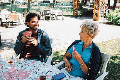 Retired senior woman playing cards with smiling male caretaker sitting at table in back yard - p426m2074256 by Maskot