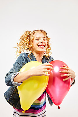 Blonde girl holding two colourful balloons - p968m1128434 by roberto pastrovicchio