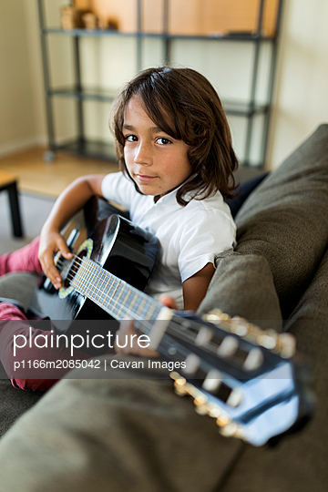 young boy  playing guitar sitting on the sofa at home - p1166m2085042 by Cavan Images