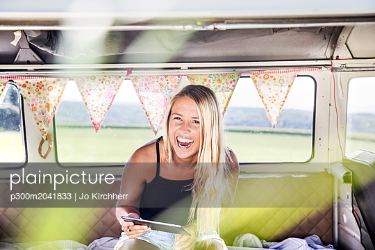 Carefree woman with tablet inside a van - p300m2041833 by Jo Kirchherr