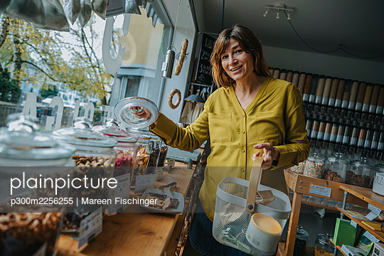 Smiling female customer with basket shopping in retail shop - p300m2256255 by Mareen Fischinger