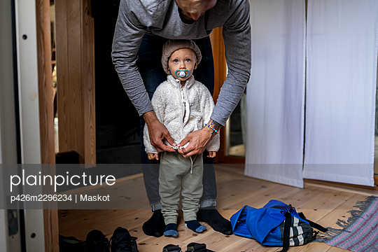 Boy getting dressed by father in mudroom at home - p426m2296234 by Maskot