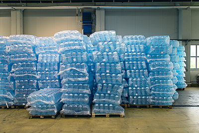 Pallets of water bottles in warehouse - p1166m2011764 by Cavan Images