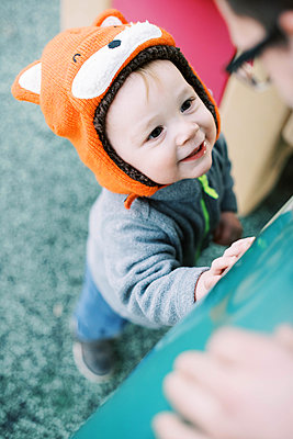 Little boy with fox hat at the playground smiling at his father. - p1166m2162852 by Cavan Images