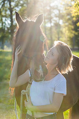Young woman with horse at backlight - p300m1459915 by Tom Chance