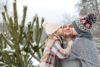 Two kids kissing their happy father at a fir tree in winter - p300m2166886 by Ekaterina Yakunina