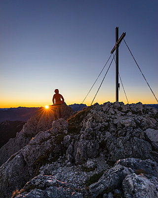 Rear view of hiker standing on viewpoint during sunrise, Gimpel, Tyrol, Austria - p300m2206847 by Matthias Aletsee