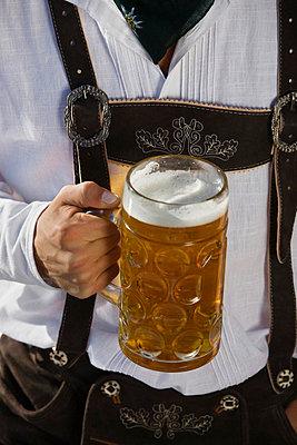 Junger Mann in Tracht steht mit Mass Bier in der Hand im Biergarten am Seehaus - p6090138f von ENGLISH photography