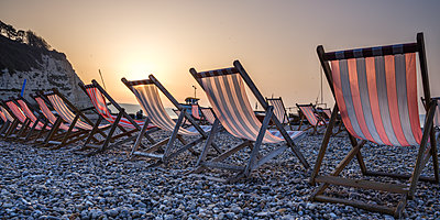 Fishing boats and deckchairs on the popular pebble beach at Beer near Seaton, Devon, England, United Kingdom - p871m2113750 by Baxter Bradford