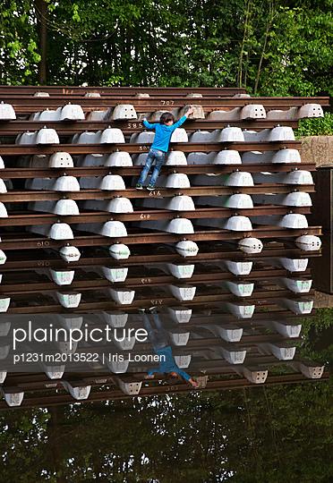 Kind klettert auf gestapeltes Baumaterial - p1231m2013522 von Iris Loonen