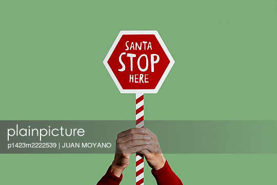 Man holding a sign that reads santa stop here - p1423m2222539 by JUAN MOYANO