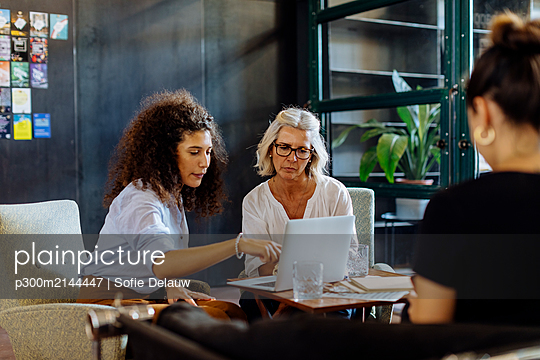 Businesswomen with laptop working together in loft office - p300m2144447 by Sofie Delauw