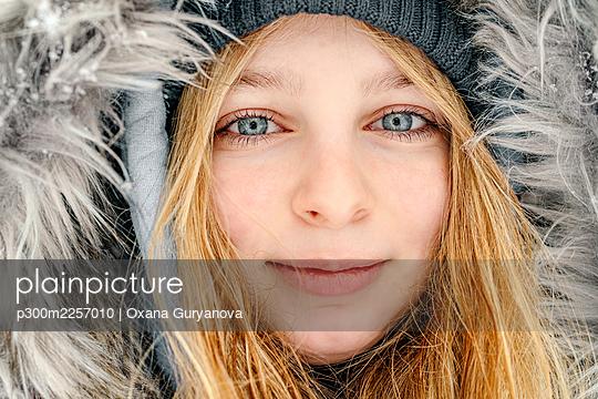 Close-up of girl wearing fur hat staring while smiling outdoors - p300m2257010 by Oxana Guryanova