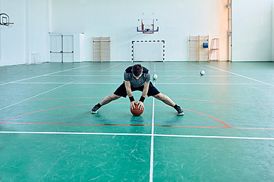 Man with basketball, stretching legs, indoor - p300m1587322 by Zeljko Dangubic