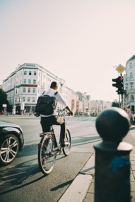 Rear view of business executive riding bicycle on road in city against sky - p426m2169389 by Maskot