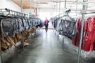 Woman between clothes rail in sewing factory sample room - p429m1175287 by Luka Storm