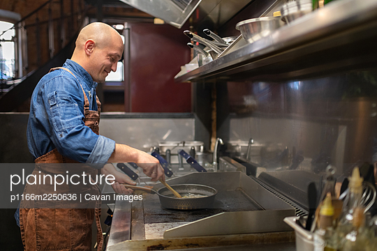 Positive cook frying food on stove - p1166m2250636 by Cavan Images