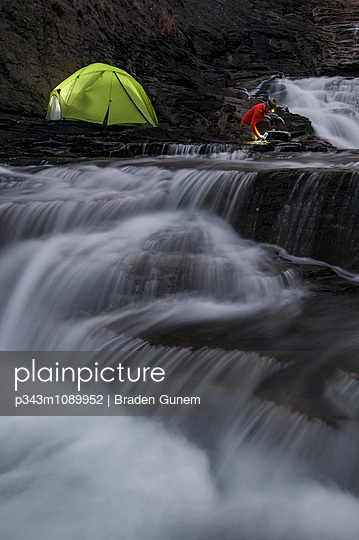 A backpacker collecting water from a stream. - p343m1089952 by Braden Gunem
