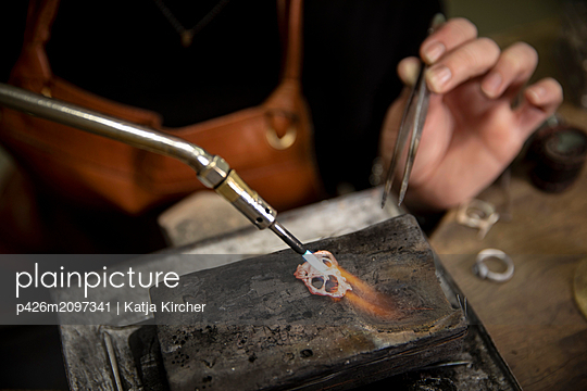 Close-up of goldsmith heating metal with welding torch to make jewelry in workshop - p426m2097341 by Katja Kircher