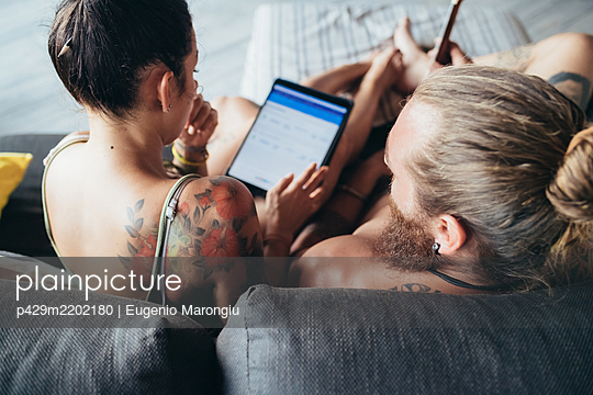 Bearded tattooed man with long brunette hair and woman with long brown hair sitting on a sofa, looking at digital tablet. - p429m2202180 by Eugenio Marongiu
