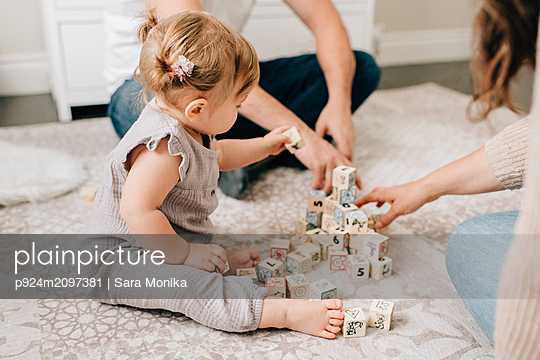 Mother and father on nursery floor with baby daughter playing with building blocks, cropped - p924m2097381 by Sara Monika