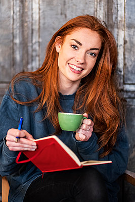 Smiling young woman with long red hair sitting at table, holding notebook and cup of coffee, looking at camera. - p1100m2010834 by Mint Images