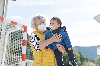 Grandmother wearing a medical mask with little grandson in her arms in a park on sunny day - p1166m2224140 by Cavan Images