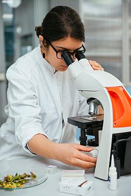 Laboratory technician using microscope in lab - p300m1416491 by Zeljko Dangubic