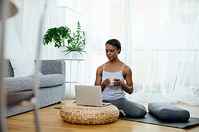 Woman sitting on gym mat at home using laptop - p300m2121886 by Sofie Delauw