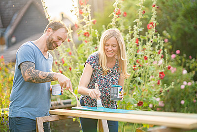 Couple painting wooden plank in garden - p300m2264562 by Annika List