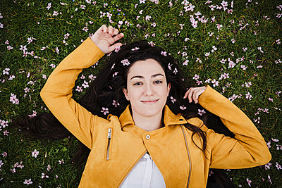 Smiling beautiful woman with flowers in hair lying on grass - p300m2274069 by Eva Blanco
