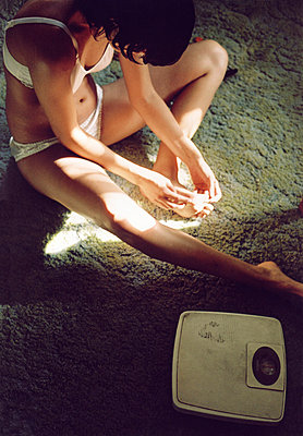 A woman in her underwear sitting on a carpet next to a scale - p3011136f by fStop