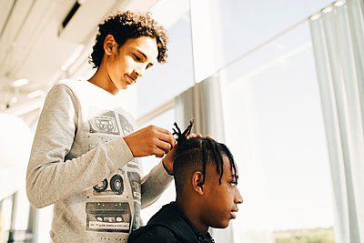 Teenage boy styling friend's hair while standing in restaurant - p426m2074883 by Maskot