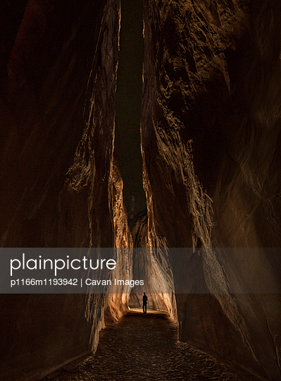 Distant view of person standing amidst rock formation - p1166m1193942 by Cavan Images
