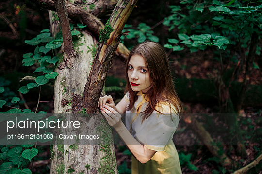 woman standing near a fallen tree in the forest - p1166m2131083 by Cavan Images