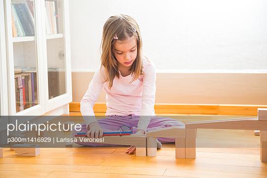Little girl crouching on floor building marble run with building bricks - p300m1416929 by Larissa Veronesi