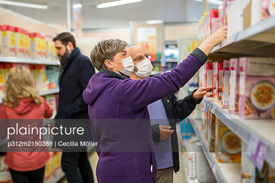 Couple wearing protective mask in supermarket - p312m2190389 by Cecilia Möller