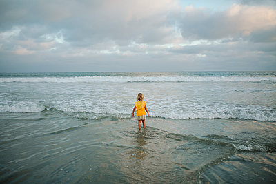 High angle view of carefree girl standing in sea at beach against cloudy sky - p1166m1509170 by Cavan Images