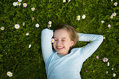 Portrait of a cheerful girl lying in the grass. - p1166m2290050 by Cavan Images