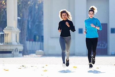 Two focused young women running listening to music - p300m1562528 by Josep Suria