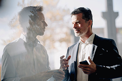 Two businessmen talking at the window - p300m2170411 by Kniel Synnatzschke