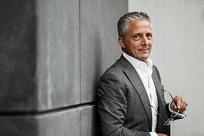 Businessman holding eyeglasses against gray wall - p300m2276382 by Sandro Jödicke