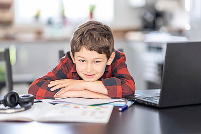 Smiling boy leaning on hand while sitting by laptop at home - p300m2282602 by William Perugini